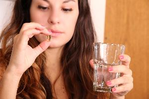 девушка держит капсулу рыбьего жира и стакан с водой в руке