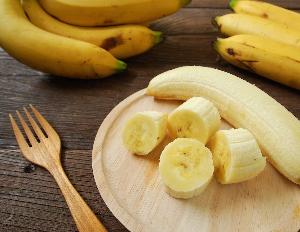 бананы целиком и кусочки на деревянной посуде