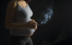беременная держит в руке дымящую сигарету