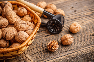 грецкие орехи в корзинке и прибор для их чистки