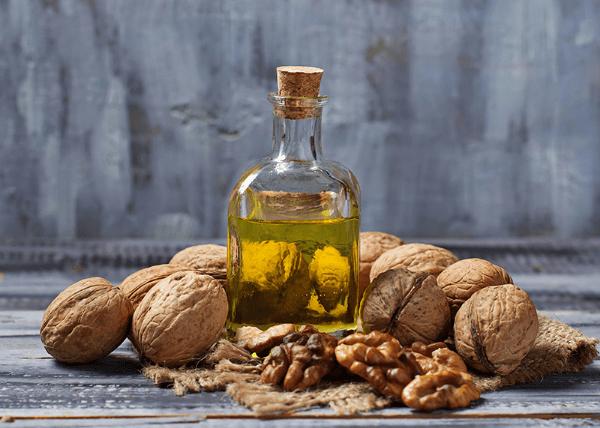 грецкий орех и мало из него в бутылочке на сером фоне