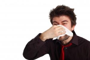 мужчина держит платок у носа
