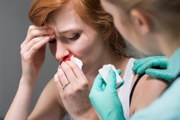 врач помогает женщине остановить кровь из носа