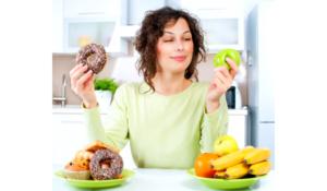 женщина выбирает между полезной едой и сладостями