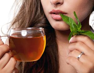 женщина держит чашку с чаем и траву
