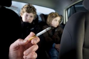 дети в машине и сигарета в руке