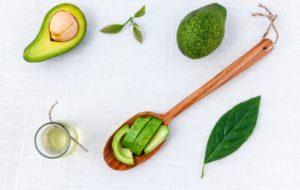 авокадо, масло, деревянная ложка на белом фоне
