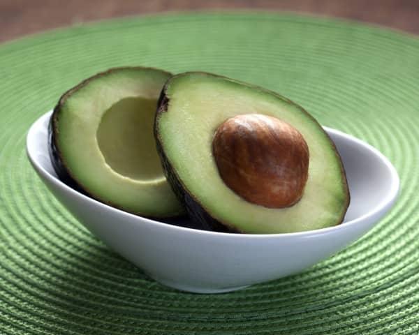 разрезанное авокадо на в тарелке