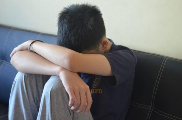мальчик сидит, опустив голову