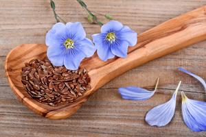 семена льна в ложке и цветы