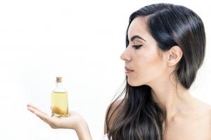 девушка держит бутылочку масла на ладони