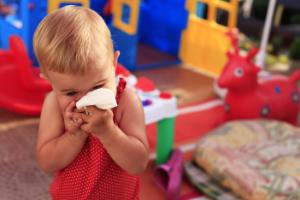 малыш на фоне игрушек с платком
