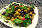 оливки с зеленью на тарелке
