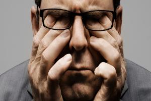 мужчина в очках держится за лицо