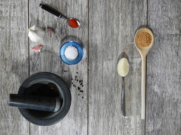 зерна горчицы, специи, чеснок и ступка