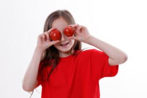 девочка держит помидоры у глаз