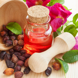 бутылочка с маслом, ступка и плоды шиповника
