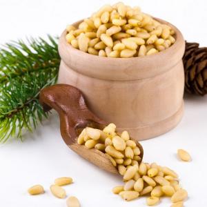 кедровые орешки в деревянной тарелке и ложке