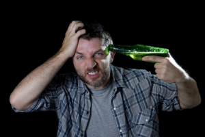 мужчина с бутылкой у виска