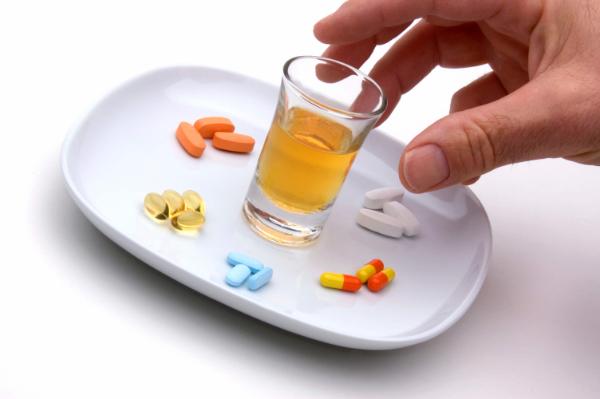 таблетки и рюмка на тарелке
