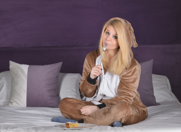 девушка сидит на кровати с пирогом