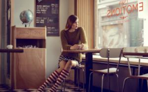 девушка сидит в кафе у окна