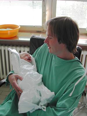 отец держит новорожденного