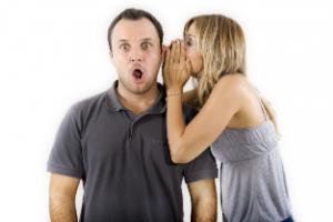 девушка говорит на ухо мужчине