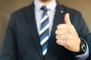 мужчина в костюме показывает большой палец