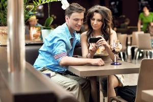 пара с телефоном в кафе