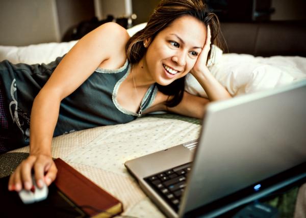 девушка, улыбаясь, смотрит в ноутбук