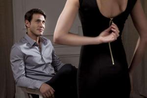 девушка расстегивает платье перед мужчиной