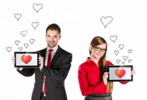 парень и девушка держат планшеты с сердечком