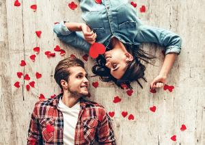 парень и девушка лежат на полу с сердечками