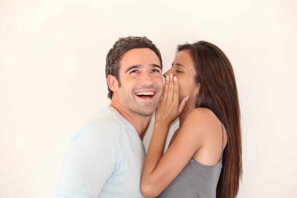 девушка шепчет на ухо парню