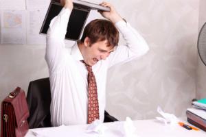 мужчина разбивает ноутбук