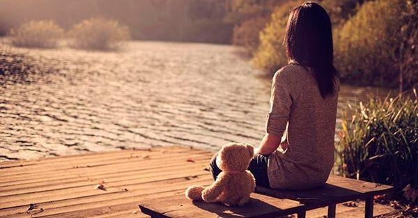 девушка с игрушкой сидит у озера