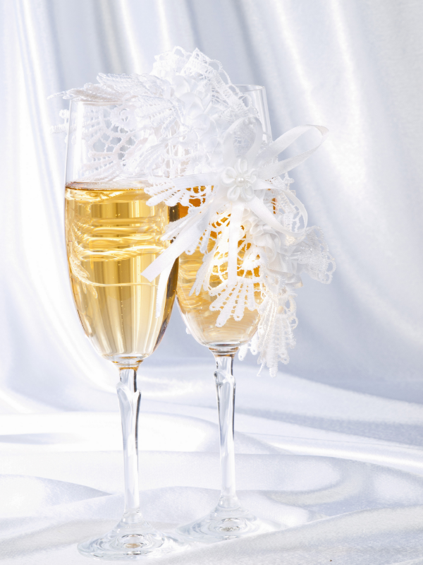 бокалы с шампанским и подвязкой на белом фоне