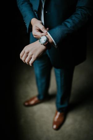 мужчина в костюме и с часами на руке